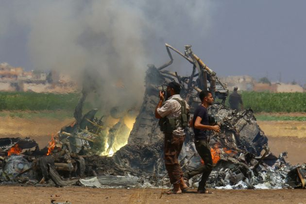 Men inspect the wreckage of a Russian helicopter that was shot down north of Syria's rebel-held...
