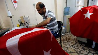 A worker makes Turkish flags at a small flag factory in Istanbul, Turkey, July 20, 2016. REUTERS/Murad Sezer
