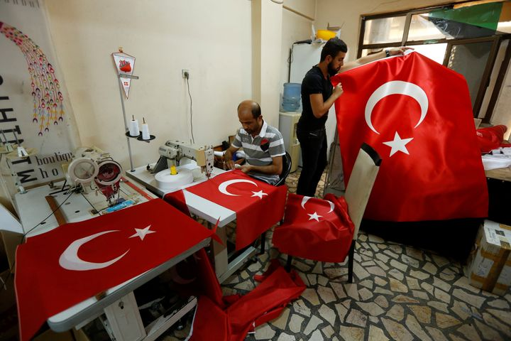Workers make Turkish flags at a small flag factory in Istanbul, Turkey. The Turkish prime minister says the government takeov