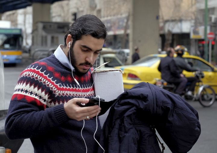 A man checks his mobile phone at a sidewalk in Tehran February 20, 2016.