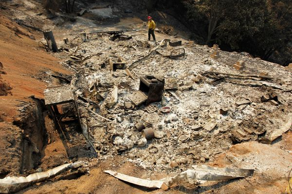 Tom Stokesberry with the U.S. Forest Service surveys a destroyed home.