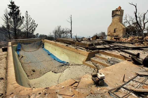 A swimming pool and a chimney remain at the site of a destroyed house.