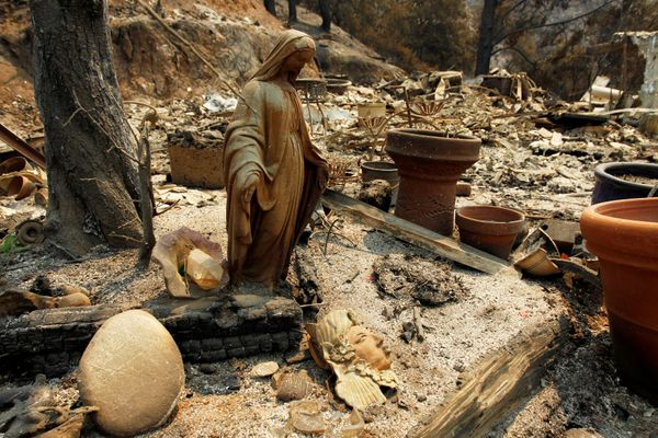 A charred Virgin Mary statue sits in a garden at the site of a destroyed home.