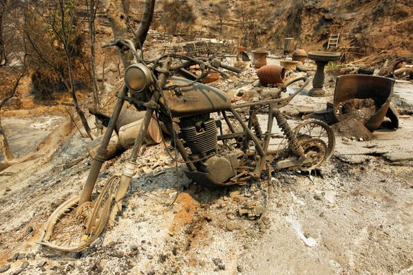 A motorcycle sits at the site of a destroyed home.