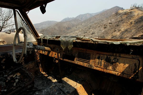 The burned landscape is seen through the cab of a vehicle.