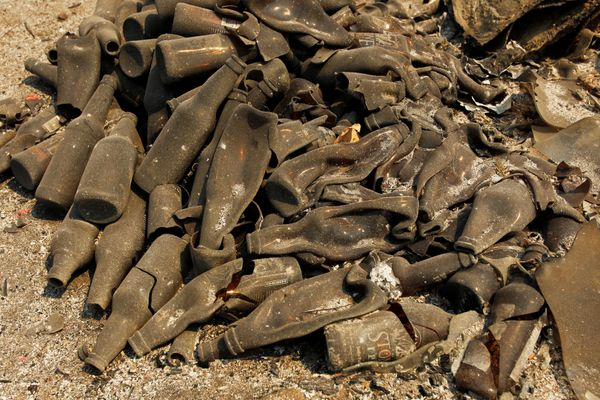 A pile of melted bottles sit on the ground.