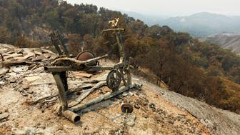 An exercise bike sits on the edge of a slope at the site of a destroyed house after the Soberanes Fire burned through the Palo Colorado area, north of Big Sur, California, U.S. July 31, 2016. REUTERS/Michael Fiala