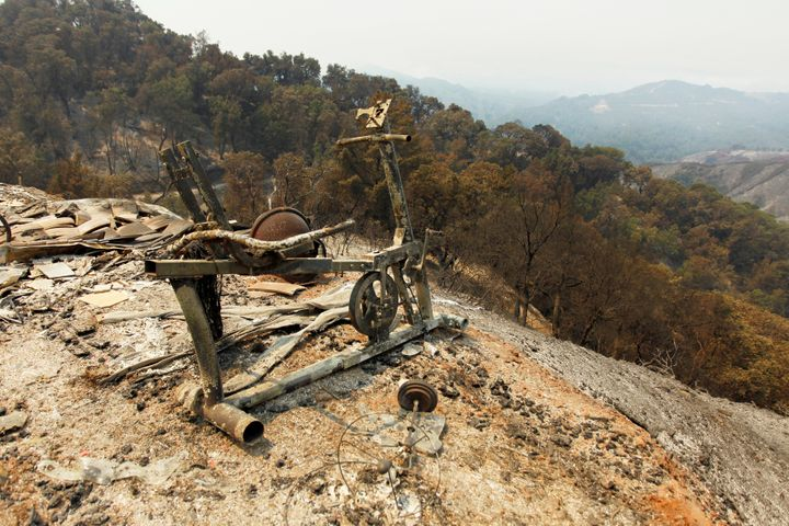A scorched exercise bike sits on the edge of a slope at the site of a destroyed house after the Soberanes fire.