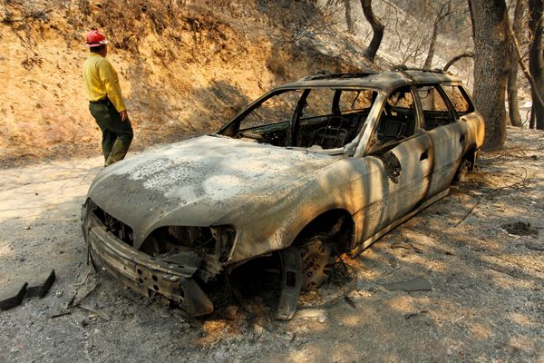 Tom Stokesberry with the U.S. Forest Service walks past a destroyed car.