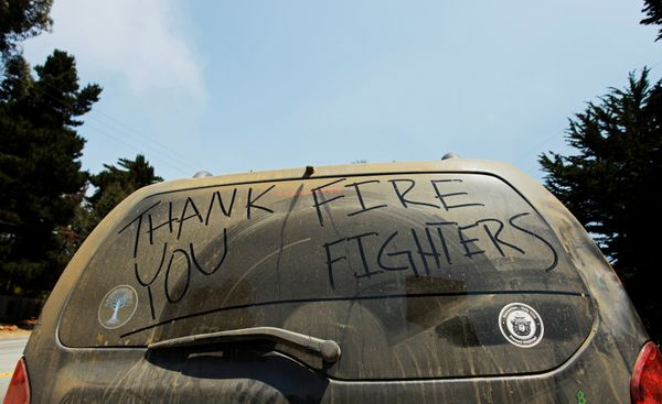 """Thank You Firefighters"" is written on the dust-covered rear window of a Big Sur resident's vehicle."