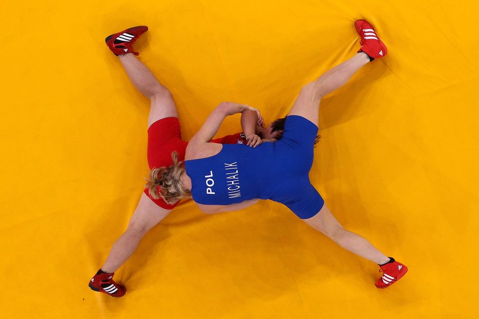 DPR Korea (red) competes against Poland (blue) in women's wrestling atthe London 2012 Olympics.