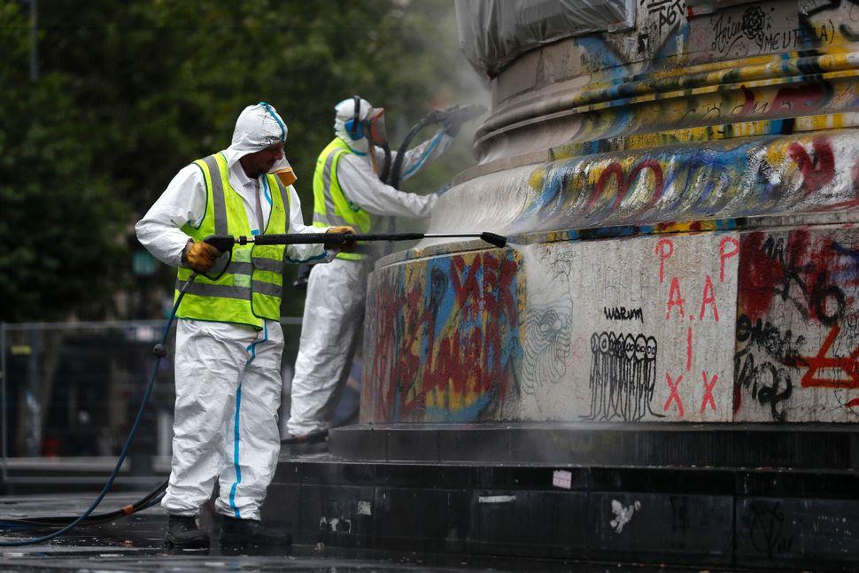 Two city employees clean graffiti off the statue of Place de la Republique in Paris, on August 2, 2016.