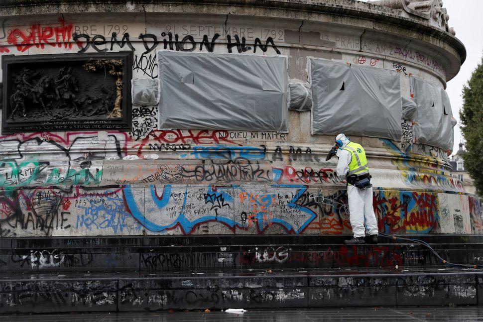 A city employee cleans graffiti off the statue of Place de la Republique in Paris, on August 2, 2016.