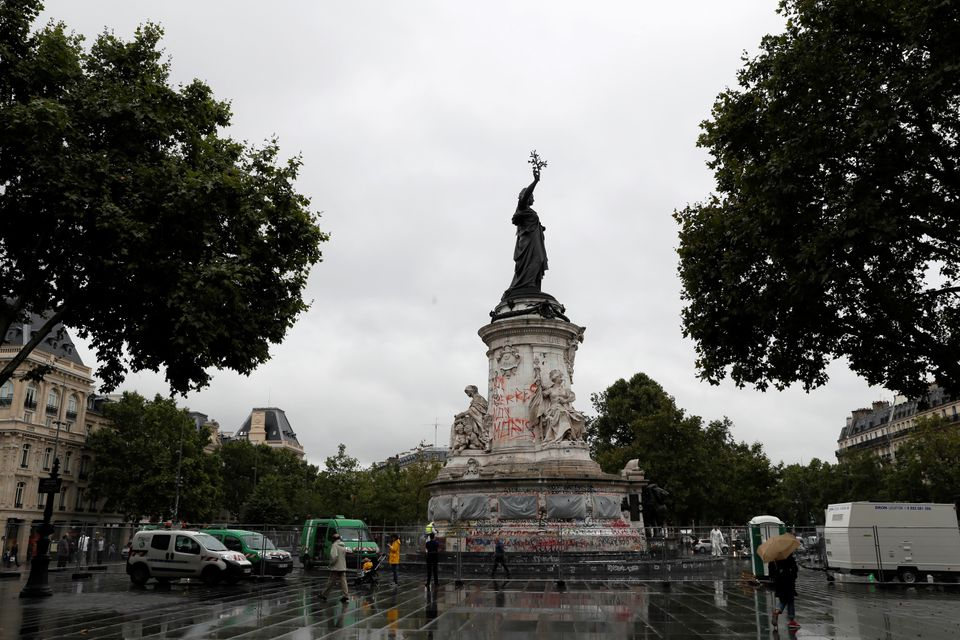 People walk by city employees as they clean graffiti off the statue of Place de la Republique in Paris, on August 2, 2016.