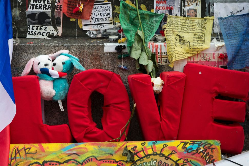 A sign reading 'Love' ispictured next to a French flag and teddy bears at a makeshift memorial for the victims of the N