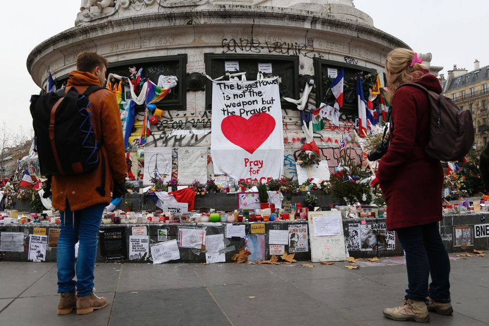 People gather in front of a makeshift memorial in Place de la Republique square in Paris on December 13, 2015.