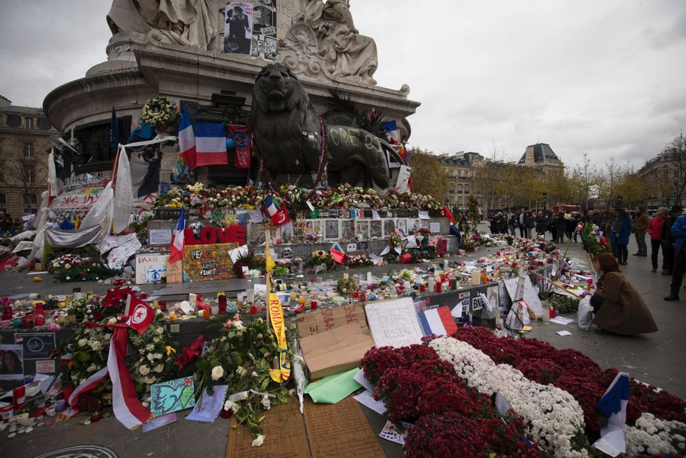 People stand in front of a makeshift memorial for the victims of the November 13 terrorist attacks, on November 30, 2015 at t