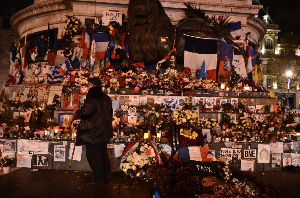 An elderly man stands in front of a makeshift memorial on Place de la Republique Paris, France, on December 11, 2015.