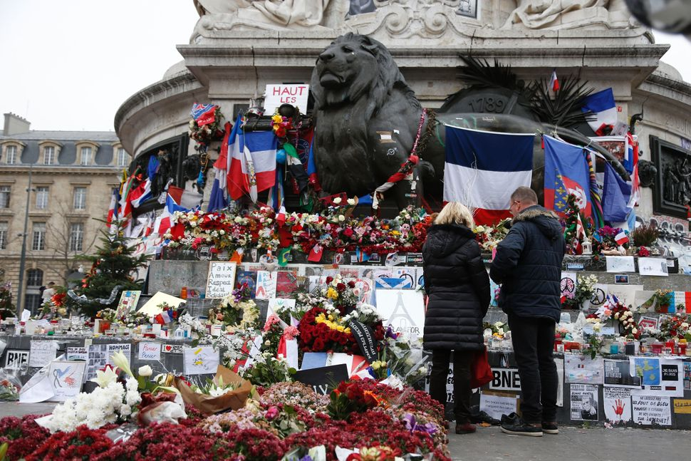 People gather in front of a makeshift memorial at the Place de la Republique in Paris on December 13, 2015, a month after the