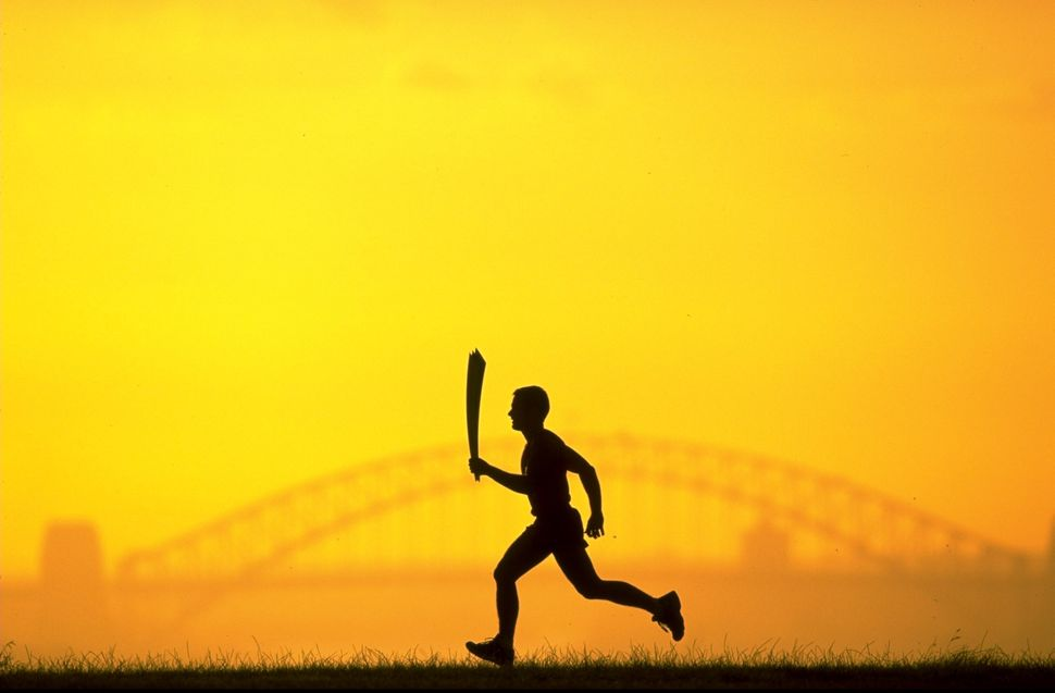 The 2000 Sydney Olympic Games Torch silhouetted against Sydney Harbour Bridge.