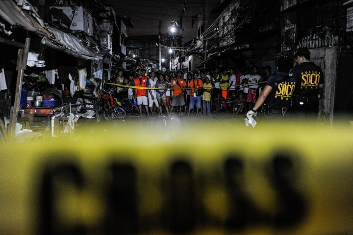 Police examine the body of an alleged drug dealer and victim of a summary execution on July 14 in Manila, Philippines.