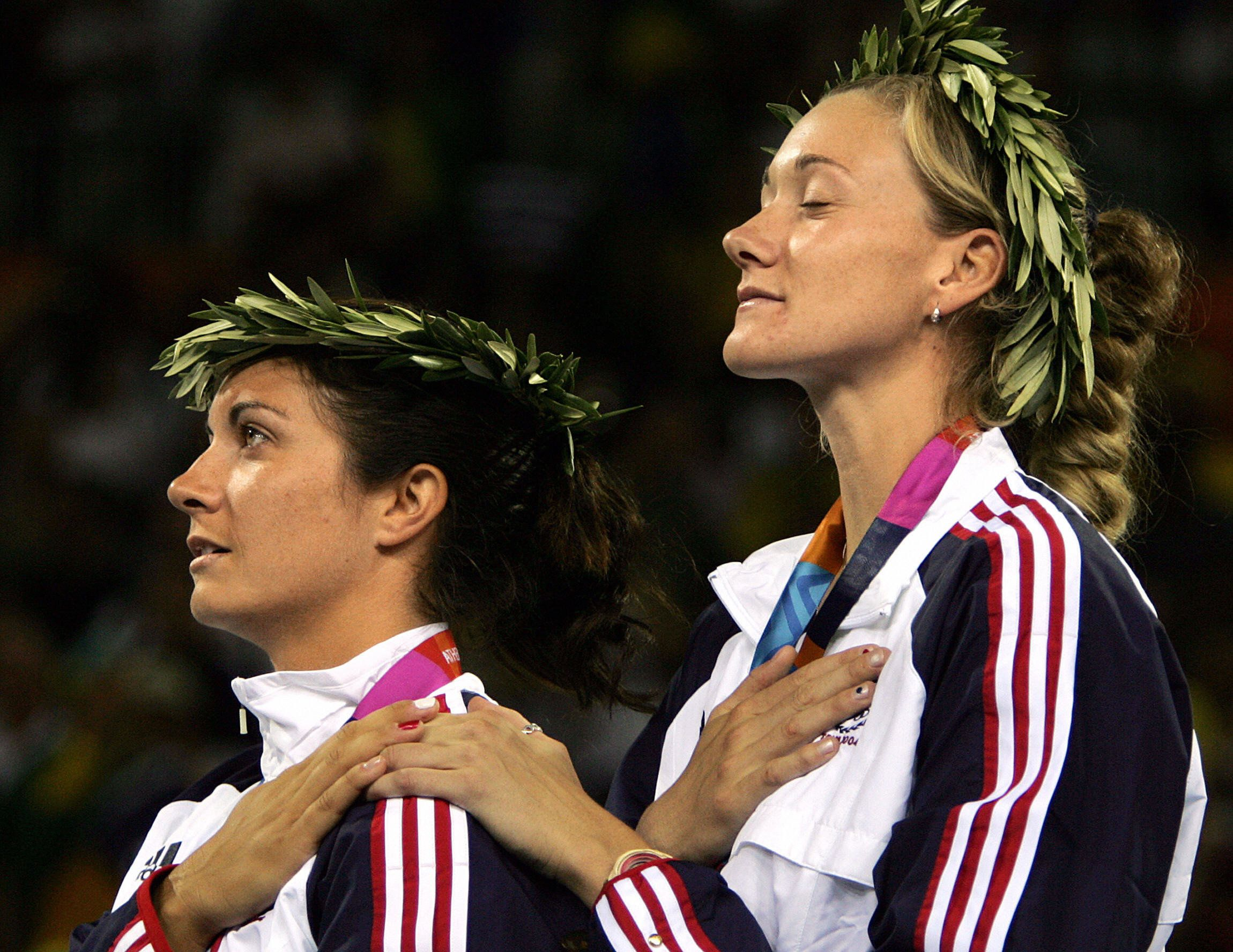 Athens, GREECE:  US beach volley players Kerri Walsh kisses (R) and Misty May celebrate their gold medal after they won over Brazilian Adriana Behar and Shelda Bede, 24 August 2004 in Athens at the 2004 Olympic Games. AFP PHOTO PHILIPPE DESMAZES  (Photo credit should read PHILIPPE DESMAZES/AFP/Getty Images)
