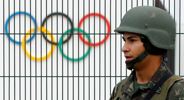 A Brazilian military police soldier patrols at the security fence outside the 2016 Rio Olympics Park...
