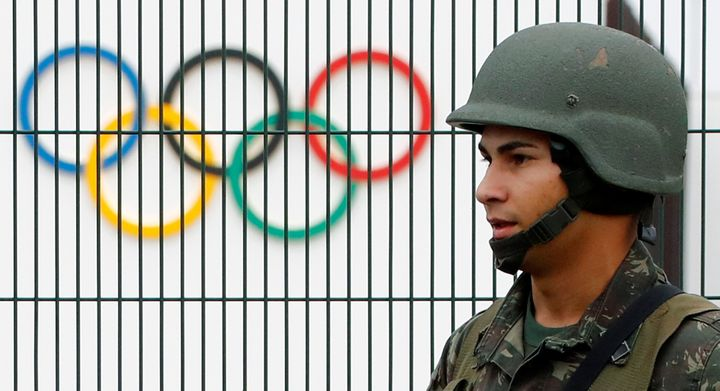 A Brazilian military police soldier patrols at the security fence outside the 2016 Rio Olympics Park in Rio de Janeiro, Brazi