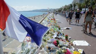 People walk past flowers left in tribute at a makeshift memorial to the victims of the Bastille Day truck attack near the Promenade des Anglais in Nice, France, July 21, 2016. REUTERS/Jean-Pierre Amet