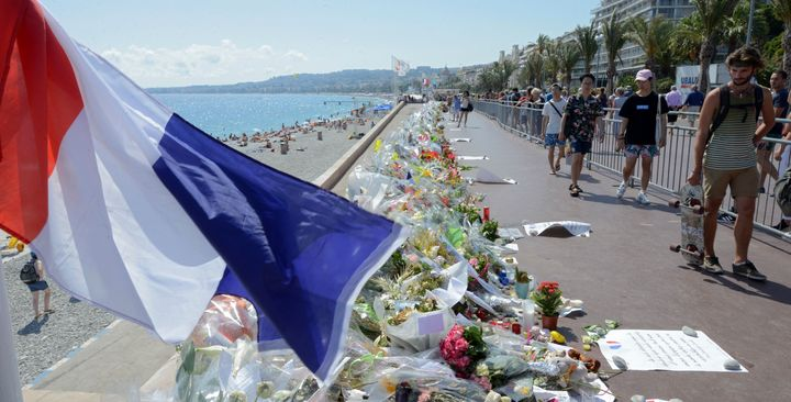 People walk past flowers left in tribute at a makeshift memorial to the victims of the Bastille Day truck attack near the Pro