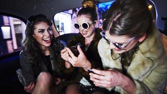 Group of young females laughing together in back of taxi, using mobile phones