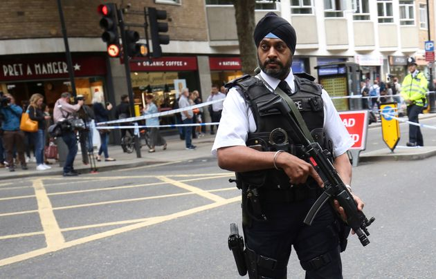 An armed officer stands guard at the scene of the knife attack in Russell Square in