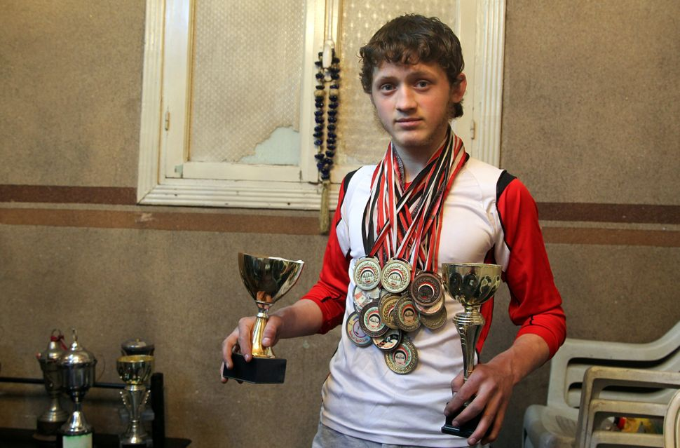 Al-Sawas poses with his medals and trophies at his home in Bustan al-Qasr in March.  Supporting the anti-