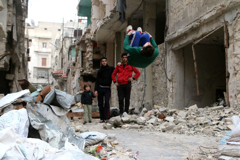 Al-Sawas performs gymnastic moves near damaged buildings in Bustan al-Qasr on March 26, 2016. He trains whereever h