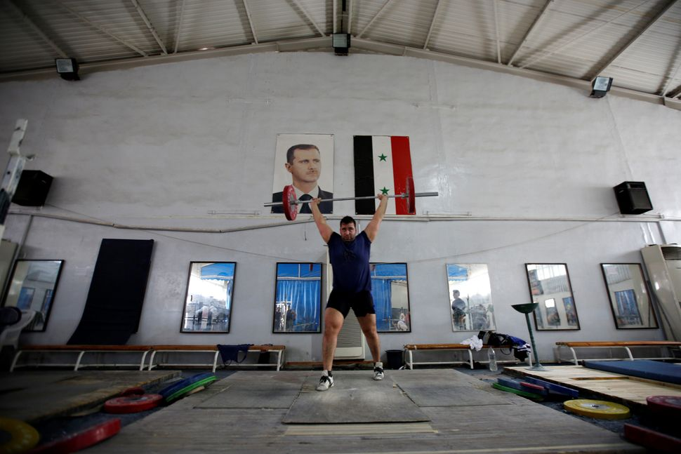 Syrian weightlifter, Man Asaad, trains for the Rio Olympics near a picture of Syrian President Bashar al-Assad and a Syrian n