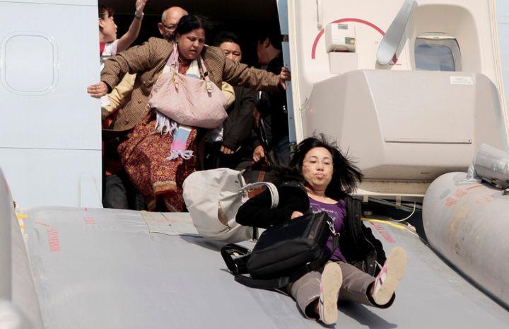 Passengers flee a Cathay Pacific Boeing 747 with their luggage