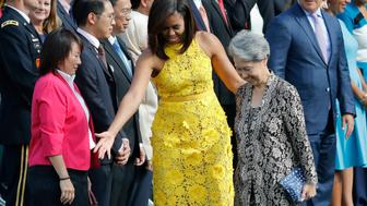 First lady Michelle Obama directs Ho Ching, right, wife of Singapore's Prime Minister Lee Hsien Loong, where to stand during a state arrival ceremony on the South Lawn of the White House in Washington, Tuesday, Aug. 2, 2016. (AP Photo/Pablo Martinez Monsivais)