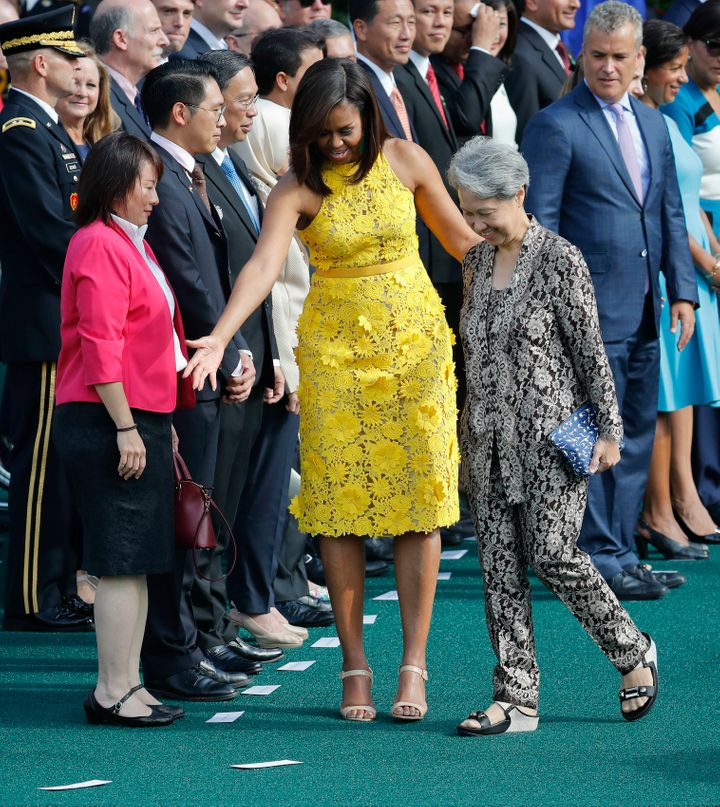 First lady Michelle Obama directs Ho Ching, right, wife of Singapore's Prime Minister Lee Hsien Loong, where to stand during