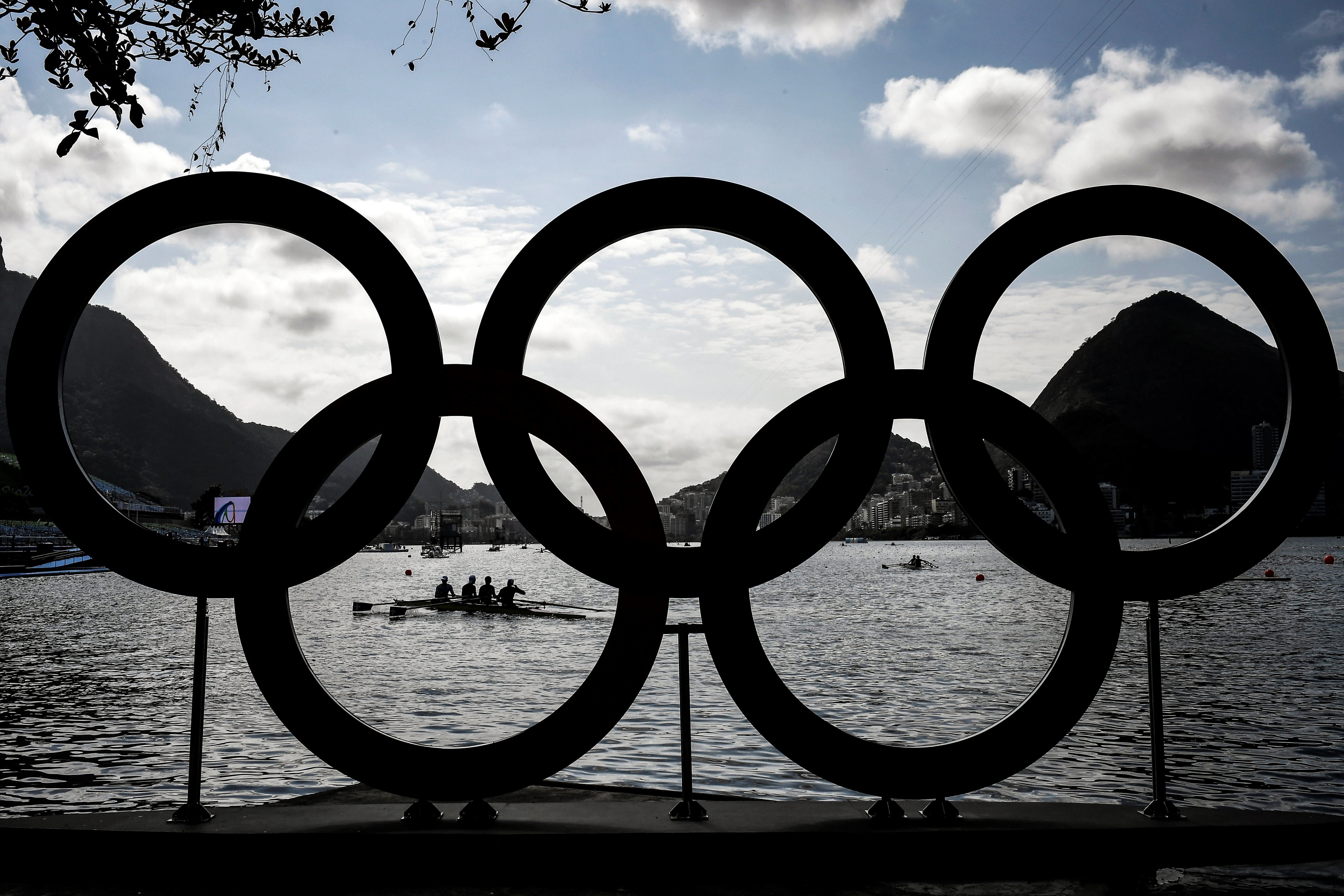 Rowers practice in front of the Olympic Rings at the Lagoa Rodrigo de Freitas ahead of the Rio 2016 Olympic Games in Rio de Janeiro on August 4, 2016.  / AFP / JEFF PACHOUD        (Photo credit should read JEFF PACHOUD/AFP/Getty Images)