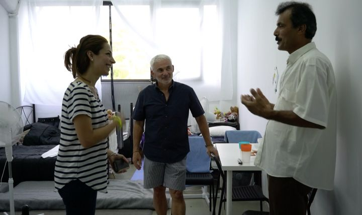 A Syrian refugee stands in one of Elpida's rooms speaking with co-founder Frank Giustra, of The Radcliffe Foundation, an
