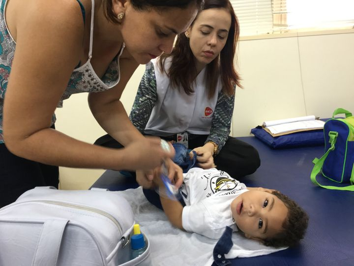 Adriana Da Silva, left, takes her son José Bernardo to the AACD clinic, where Dr. Ana Patrícia, right, treats h