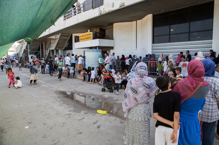 Refugees wait in line for vaccines.