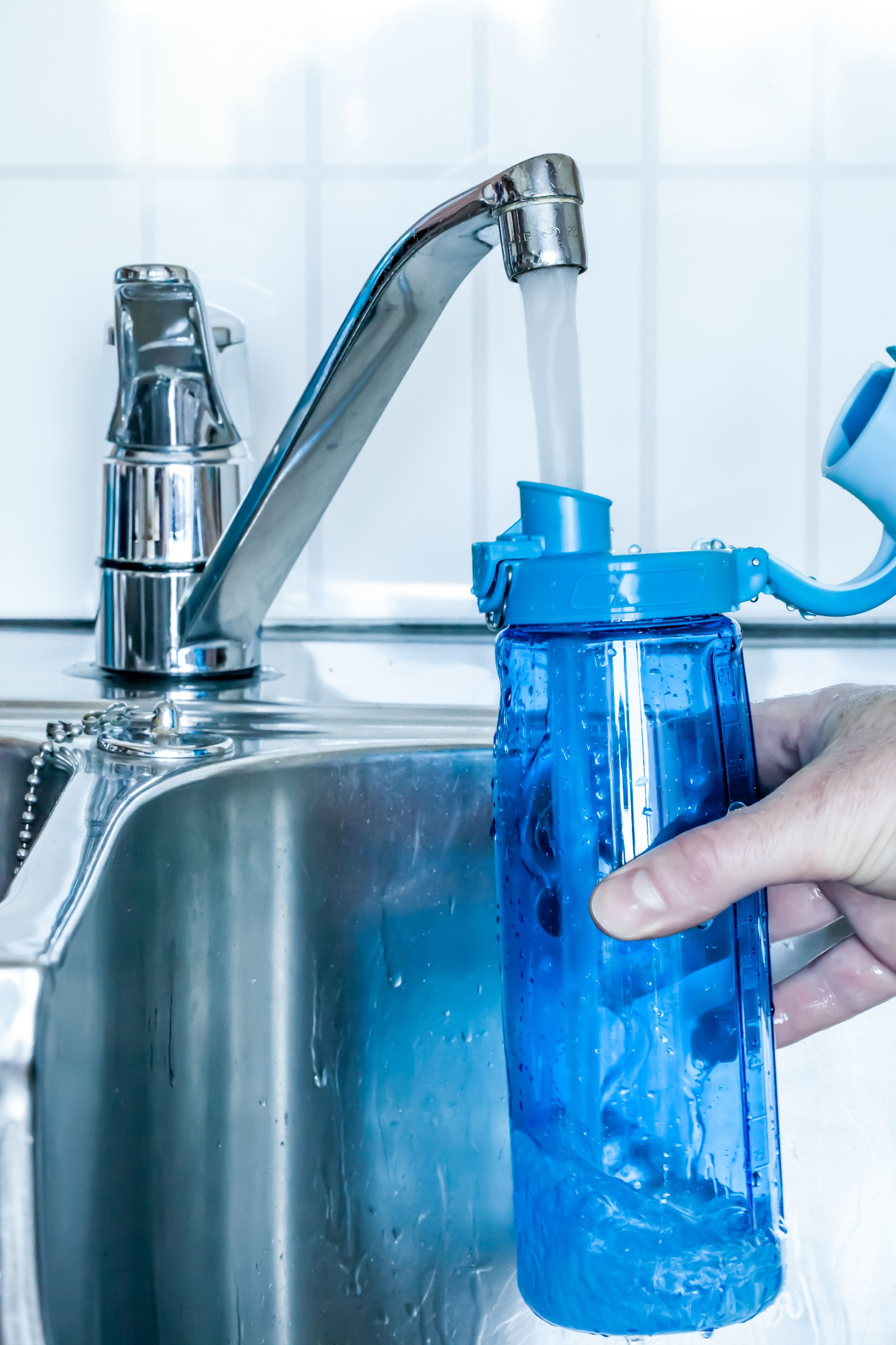 Filling fresh and cold water in a drinking bottle.