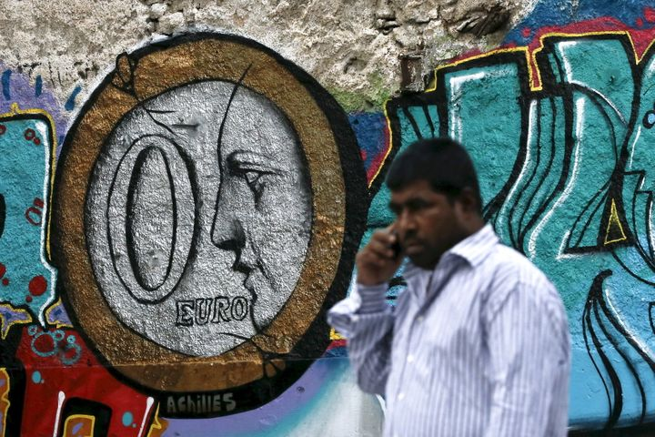 A man walks past a graffiti by Greek street artist Achilles, depicting a zero Euro coin in Athens on June 26, 2015.