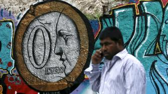 A man walks past a graffiti by Greek street artist Achilles, depicting a zero Euro coin in Athens, Greece, June 26, 2015. Greece failed again to clinch a deal with its international creditors on Thursday, setting up a last-ditch effort on Saturday to avert a default next week or start preparing to protect the euro zone from financial market turmoil. REUTERS/Alkis Konstantinidis
