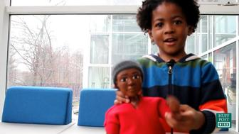 A young boy plays with a prototype of Melanites, a new line of dolls for boys of color.