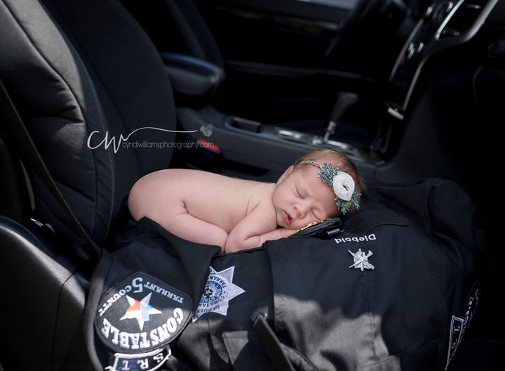 Evelyn posedwiththe officer's uniform in the front seat of her parents' car -- the exact spot where she was born.