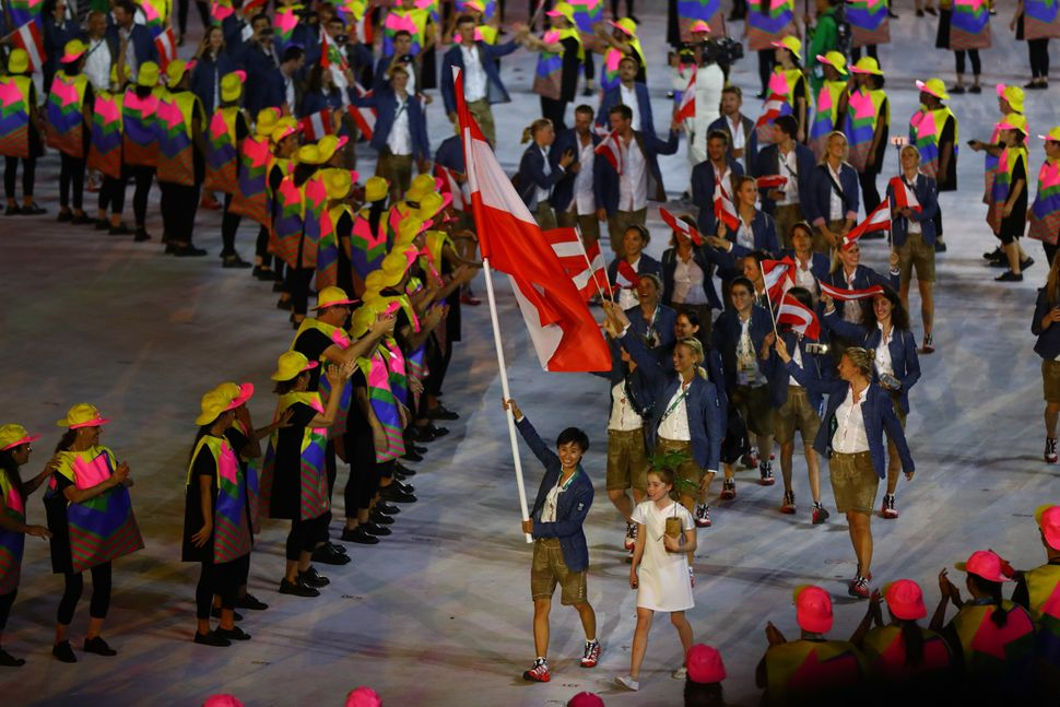 Jia Lui of Austria carries her country's flag during the Opening Ceremony.