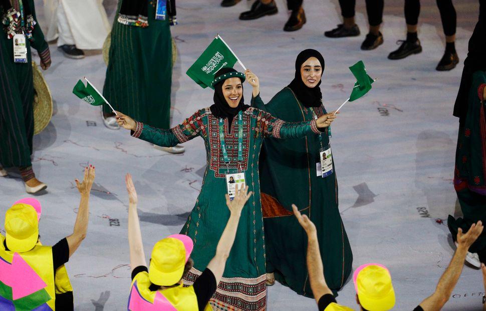 Sarah Attar (KSA) of Saudi Arabia waves flags during the opening ceremony.