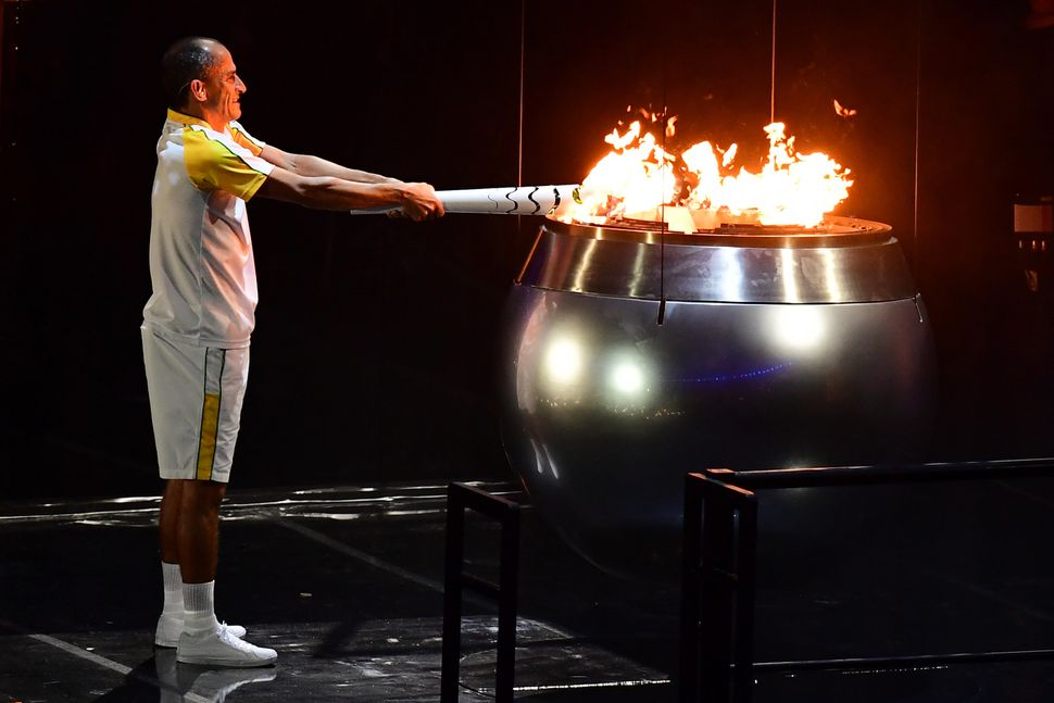 Former Brazilian athlete Vanderlei Cordeiro lights the Olympic cauldron with the Olympic torch during the opening ceremony of